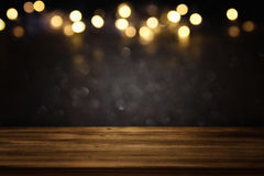 Empty table in front of black and gold glitter lights background. For product display montage Royalty Free Stock Photos