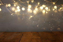 empty table in front of Christmas warm gold garland lights Stock Photo