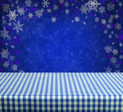 Empty table. Empty gingham table with blue christmas background Royalty Free Stock Image