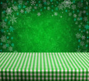 Empty table. Empty gingham table with green christmas background Royalty Free Stock Image