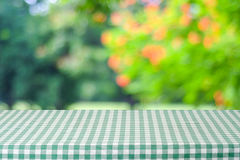 Empty table with green tablecloth over blur garden and bokeh bac Stock Image