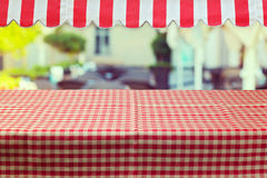 Empty table with red checked tablecloth and awing Stock Image