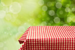 Empty table with red checked tablecloth over green bokeh background.