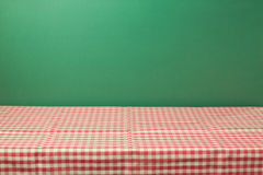 Empty table with red checked tablecloth over green wall. Background Stock Images