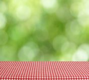 Empty table red checkered tablecloth. Blurred green background. Place for presentation stock photography