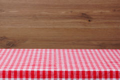 An empty table with a red checkered tablecloth. Wooden background. Royalty Free Stock Photography