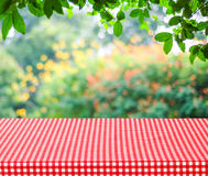 Empty table and red tablecloth with blur green leaves bokeh back Royalty Free Stock Photos