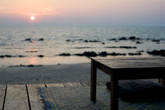 Empty table - rustic beach bar at sunset. Relaxing scene of empty table and cushion for sitting on the deck of a simple beach bar.  Andaman Islands, Thailand Stock Image