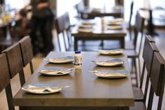 Empty table and seats in restaurant. Empty table and seats in the restaurant. Plates are ready for new customers Royalty Free Stock Images
