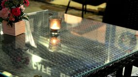 Empty table of a street cafe at night with a burning tea light candle and roses in a wood box. Selective focus stock footage