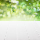 Empty table in a summer garden. Empty table in a sun drenched summer garden for product placement with focus to the table top in the foreground Royalty Free Stock Image
