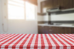 Empty table with tablecloth and blurred kitchen background, product montage display.  Royalty Free Stock Images