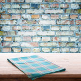Empty table and tablecloth, gray brick wall as background. stock photos