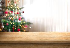 Empty table top and christmas tree in background. Empty wood table top and blur of room with a christmas tree background, suitable for montage product display stock image