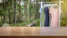 Concept for organic clothes and sustainable fashion. Hanger with dresses blurred in. Empty table top for product display montage. Concept for organic clothes and stock images