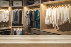Fashion and clothes concept. Walk in closet wardrobe blurred in the background royalty free stock photography