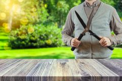 Gardener holding a hedgecutter blurred in the background. Gardening concept stock images
