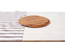 Empty tablecloth on wood table and pizza cutting board isolated on white background. Selective focus. Place for food. Top view. Mockup and template copy space stock images