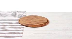 Empty tablecloth on wood table and pizza cutting board isolated on white background. Selective focus. Place for food. Top view. Mockup and template copy space stock image