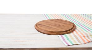 Empty tablecloth on wood table and pizza cutting board isolated on white background. Selective focus. Place for food. Top view. Empty tablecloth on wood table royalty free stock photography