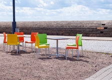 Empty tables and beautiful colourful plastic chairs in a street Stock Image