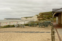 Empty tables at Birling Gap, Eastbourne. Some empty tables in front west coastline with cliffs and beaches at touristic location of Birling Gap, Eastbourne stock image