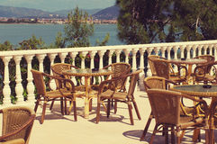Empty tables and chairs on the coast against the sea and mountains Stock Images