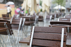 Empty tables and chairs in front of a restaurant in the rain Stock Image