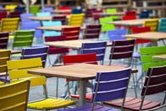 Empty  tables and coloured chairs in a street Royalty Free Stock Photos