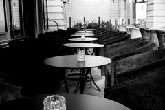 Empty tables waiting for clients. Black and white photography of empty table rows with chairs waiting for clients Royalty Free Stock Image