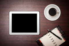 Empty tablet and a cup of coffee in office Stock Images