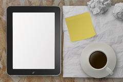 Empty tablet pc and cup of coffee with stickly note on crumple p Royalty Free Stock Photos