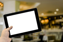 Empty tablet PC in hand in cafe bar interior Royalty Free Stock Photos