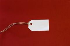Empty tag blanco en un fondo rojo Fotografía de archivo libre de regalías