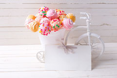 Empty tag and bright cake pops  in decorative bicycle on white w Royalty Free Stock Photo