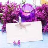 Empty tag, flor aromática fresca de la lila y vela en woode azul Fotografía de archivo