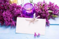 Empty tag, flor lilás aromática fresca e vela no woode azul Imagem de Stock Royalty Free