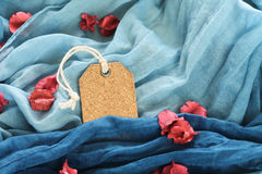Empty Tag label and red flower put on blue scarf Stock Photos