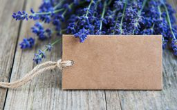 Empty tag and lavender flowers. On a old wooden table royalty free stock image