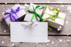 Empty tag and three festive gift boxes with presents on vintage Stock Images