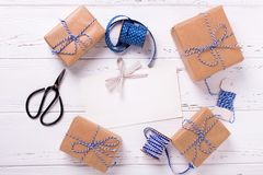 Empty tag and wrapped  gift boxes with presents, scissors,  blue. Ribbon  and tags on textured wooden background. Selective focus. Place for text. Flat lay Royalty Free Stock Image