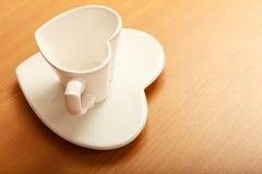 Empty tea coffee cup mug on saucer. Heart shape. Stock Photography