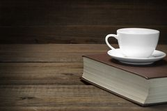 Free Empty Tea Cup On The Red Old Book In Dark Royalty Free Stock Photography - 65189777