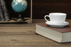 Empty Tea Cup On The Red Old Book And Bookshelf Royalty Free Stock Image