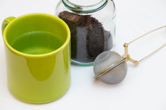 Empty tea infuser and a jar of tea next to each other Stock Photo