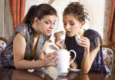 Empty teapot. Two girlfriends have already drunk tea and look in an empty teapot stock images