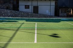 An empty tennis court, with a grassy surface and a protective ne royalty free stock images