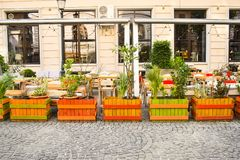 Empty terrace on the sidewalk with beautiful flowers fence in the Bucharest`s Historical Downtown. Bucharest, Romania - 21.05.201 royalty free stock photos
