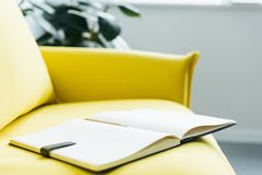 Empty textbook pages with pencil on yellow. Leather couch royalty free stock photography