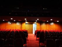 The empty theater hall with the extinguished lights. Only the back lights on the wall lit royalty free stock photography